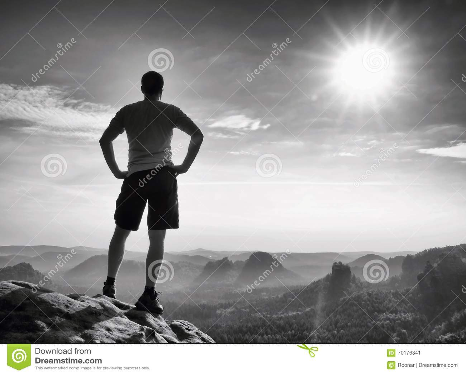 Den lyckliga fotvandraren står på den skarpa klippan vaggar in väldear parkerar och hålla ögonen på över den dimmiga och dimmiga