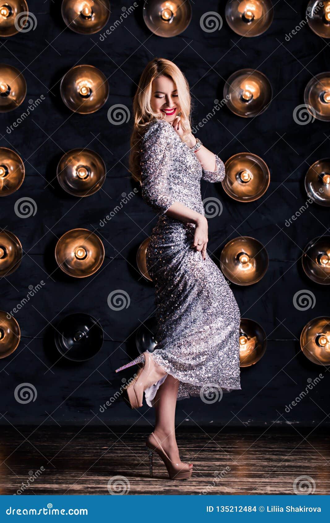 Den lyckliga glade blonda kvinnan i ett långt försilvrar klänningen på en svart bakgrund Beröm parti, nytt år, födelsedag