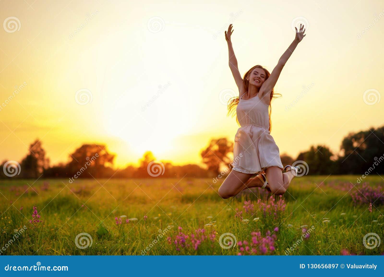 Den lyckliga gladlynta flickan hoppar på naturen över sommarsolnedgången