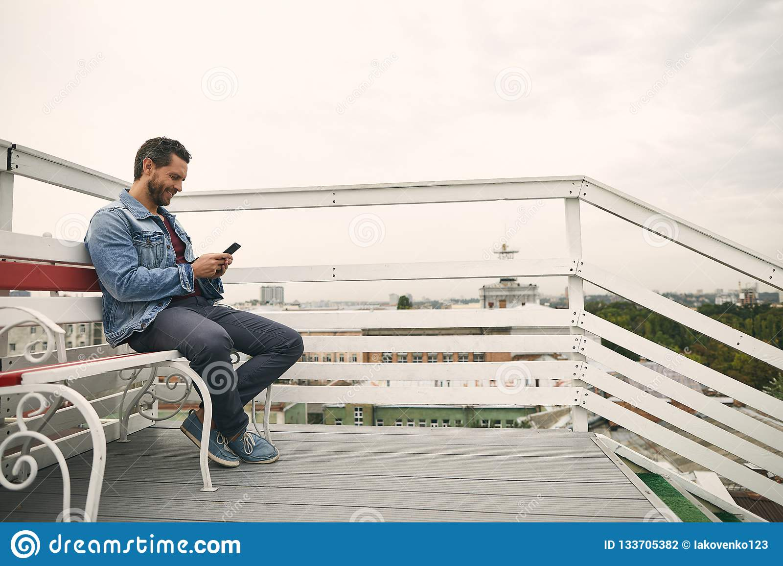 Den lyckliga grabben sitter på gullig terrass utomhus