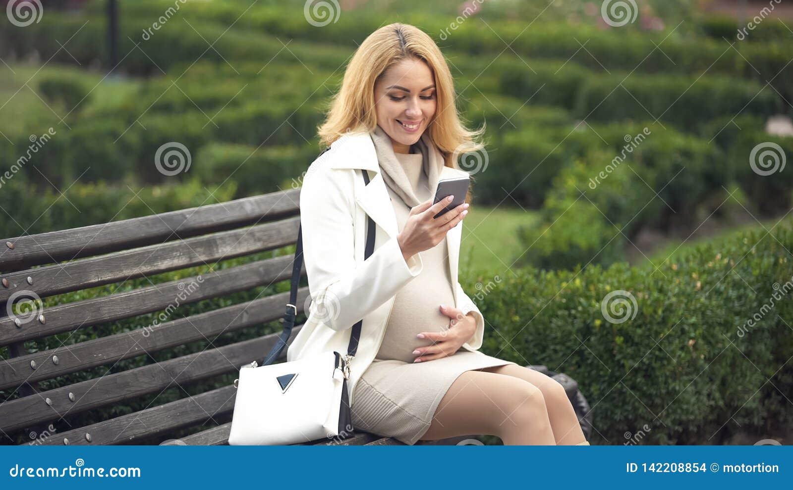 Den lyckliga gravida kvinnan som sitter på, parkerar bänken med smartphonen som slår buken
