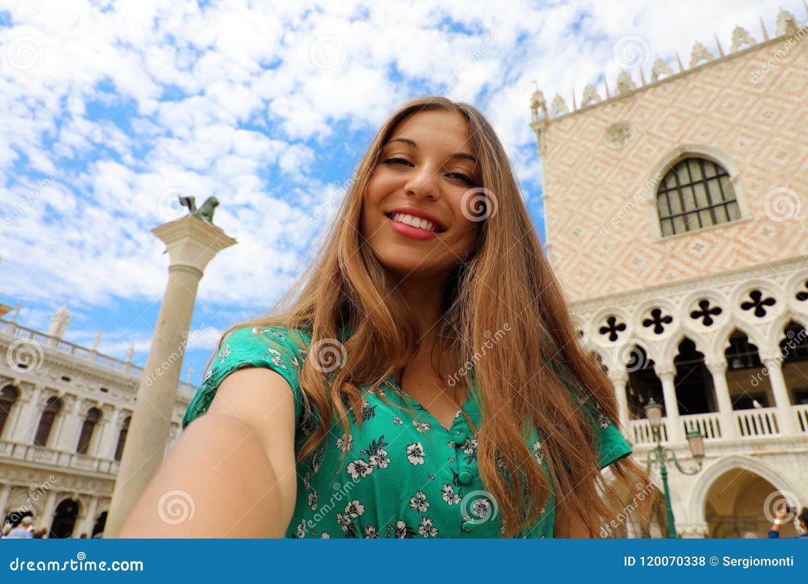 Den lyckliga härliga kvinnan som tar selfiefotoet i Venedig med vit, fördunklar i himlen Turist- flicka som ler på kameran