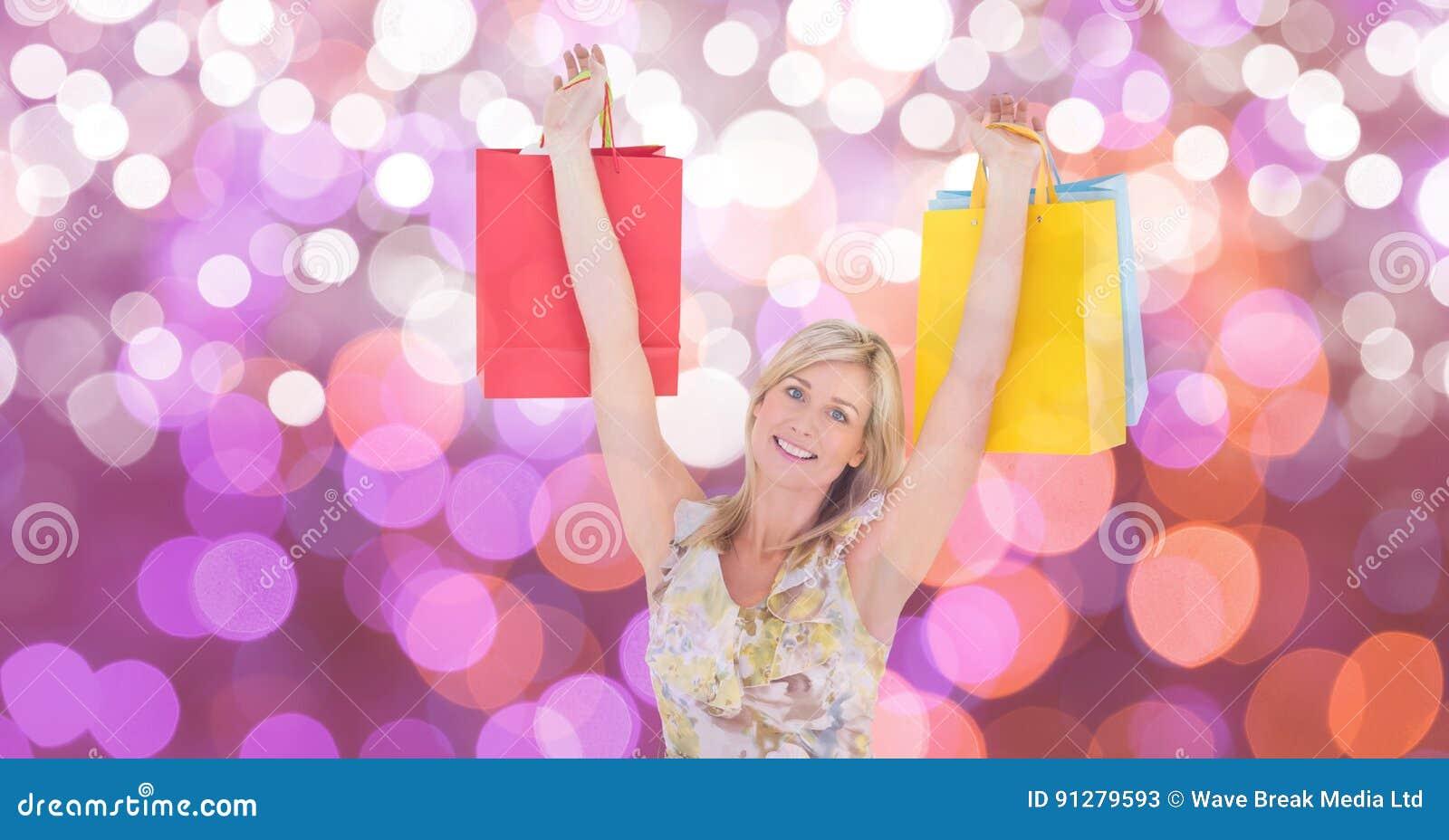 Den lyckliga kvinnan med armar lyftte bärande shoppingpåsar över bokeh