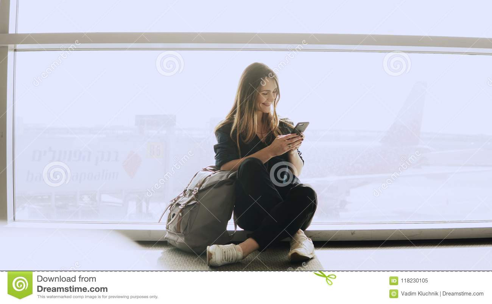 Den lyckliga kvinnan sitter med smartphonen vid flygplatsfönstret Caucasian flicka med ryggsäcken genom att använda budbäraren ap