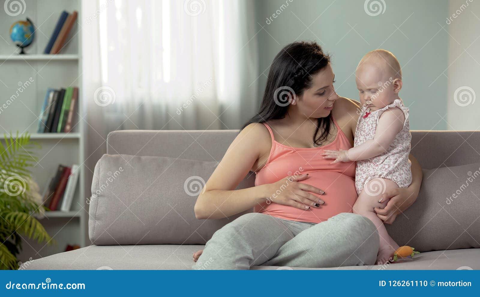 Den lyckliga kvinnan som i andra hand förväntar, behandla som ett barn och att berätta det första barnet om broder eller syster