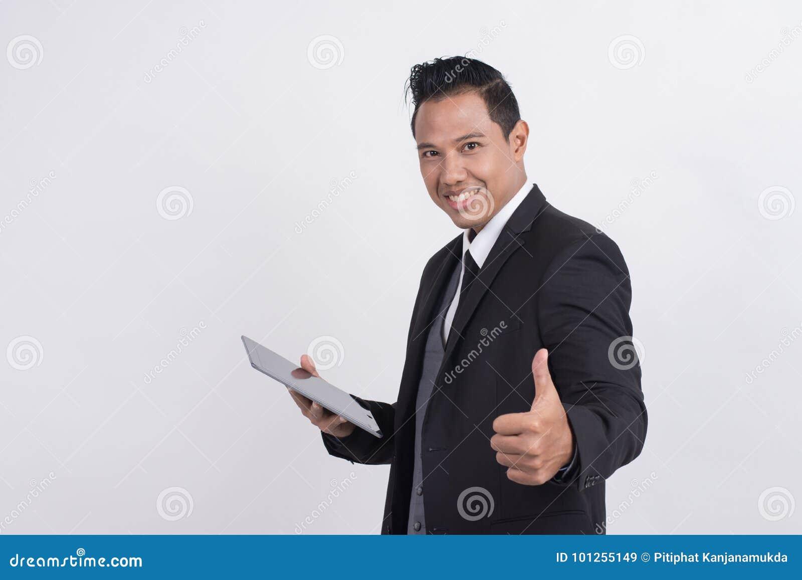 Den lyckliga le asiatiska affärsmannen med tummar gör en gest upp se kameran