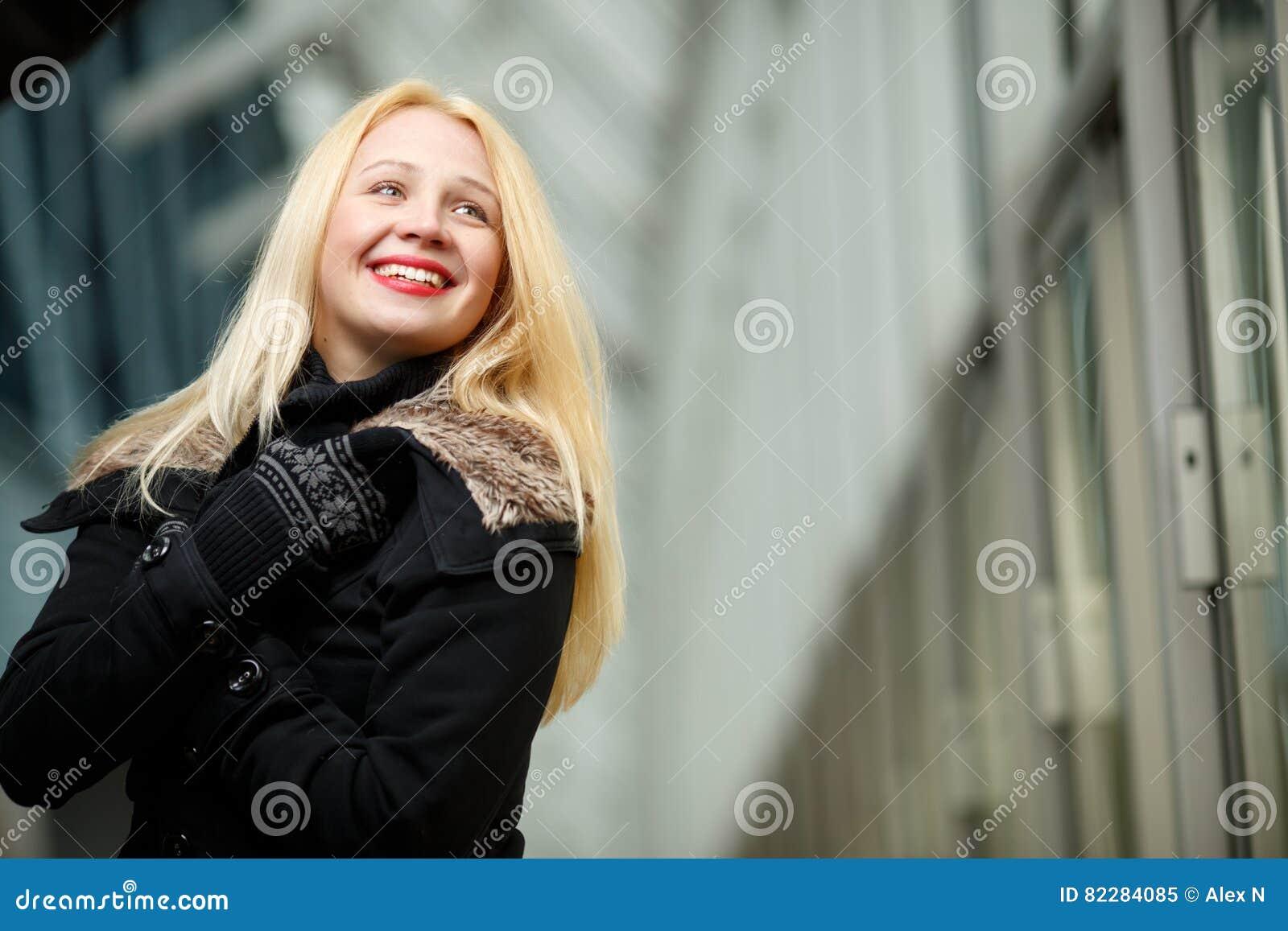 Den lyckliga le blonda kvinnan i svart klår upp ner och tumvanten