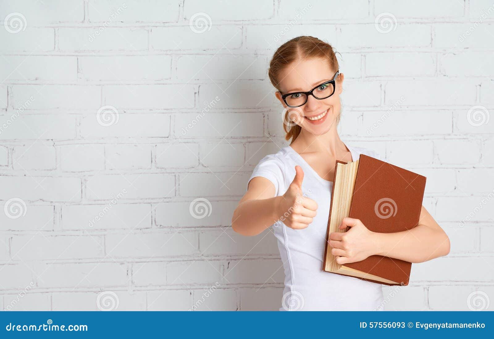 Den lyckliga lyckade studentflickan med bokvisning tummar upp