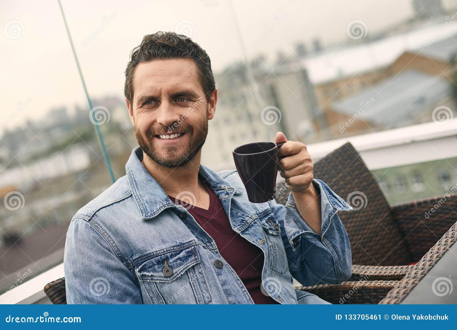 Den lyckliga mannen rymmer koppen i hand