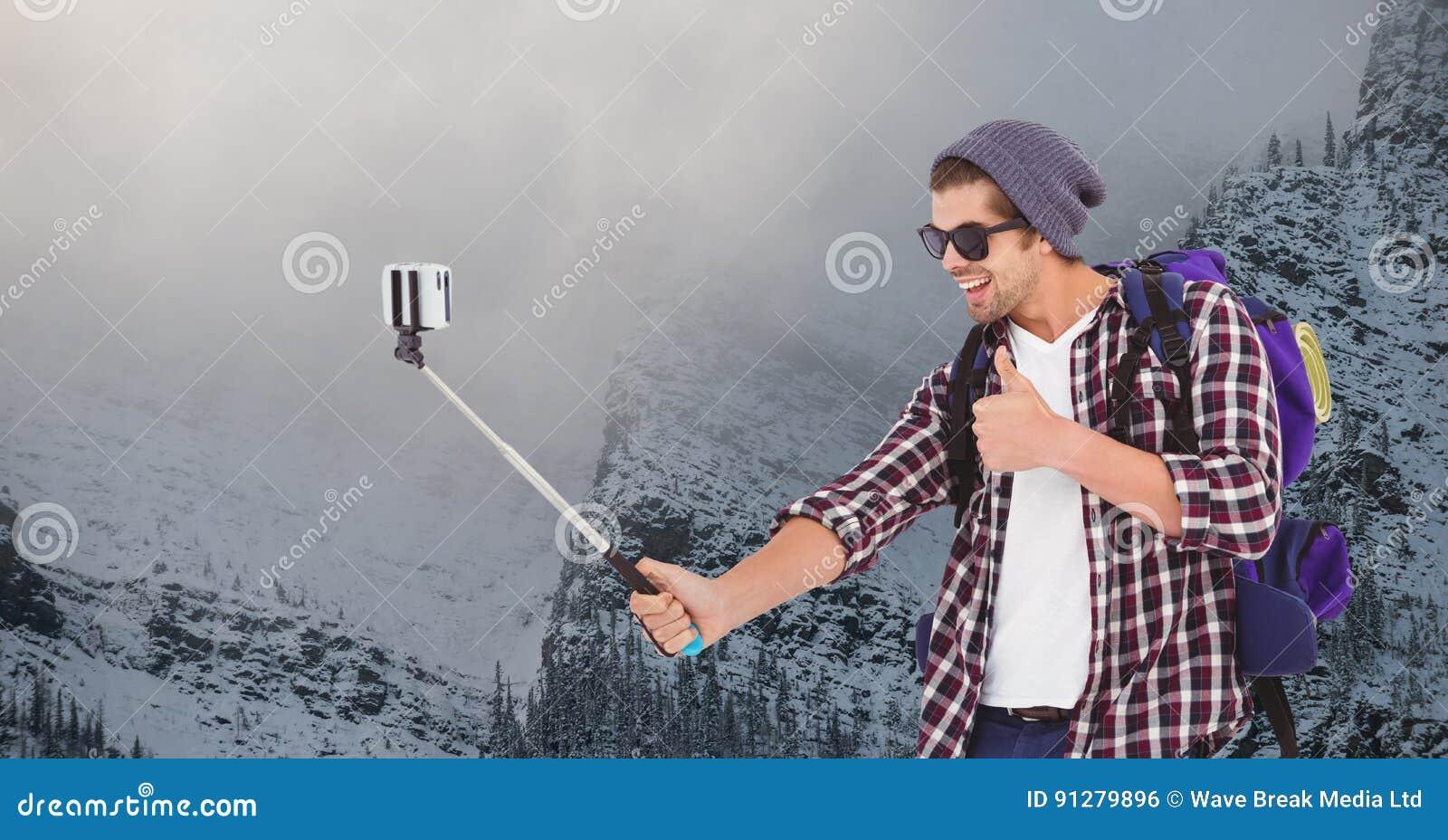 Den lyckliga mannen som tar selfie på den smarta telefonen mot snö, täckte berget