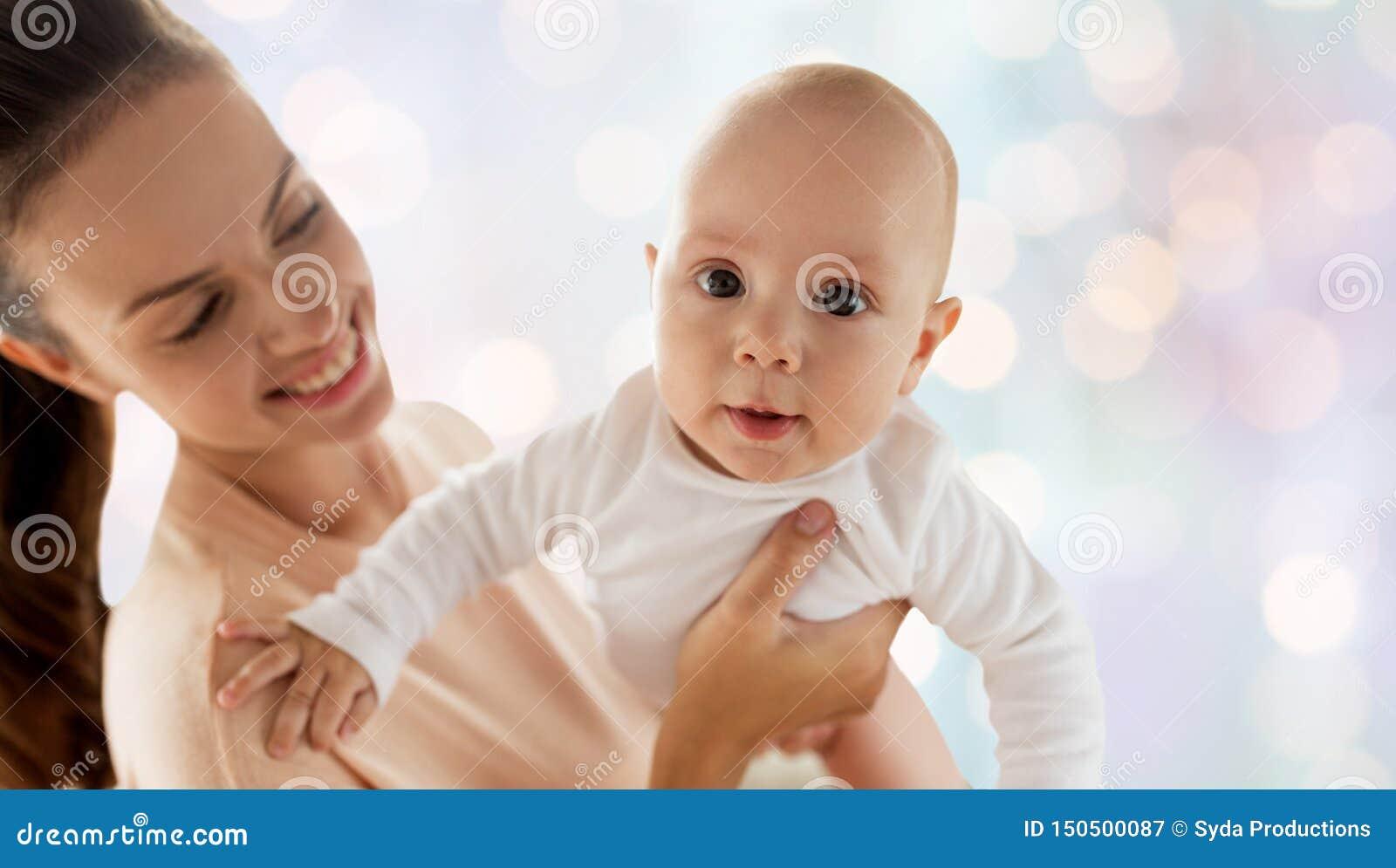 Den lyckliga modern med litet behandla som ett barn pojken