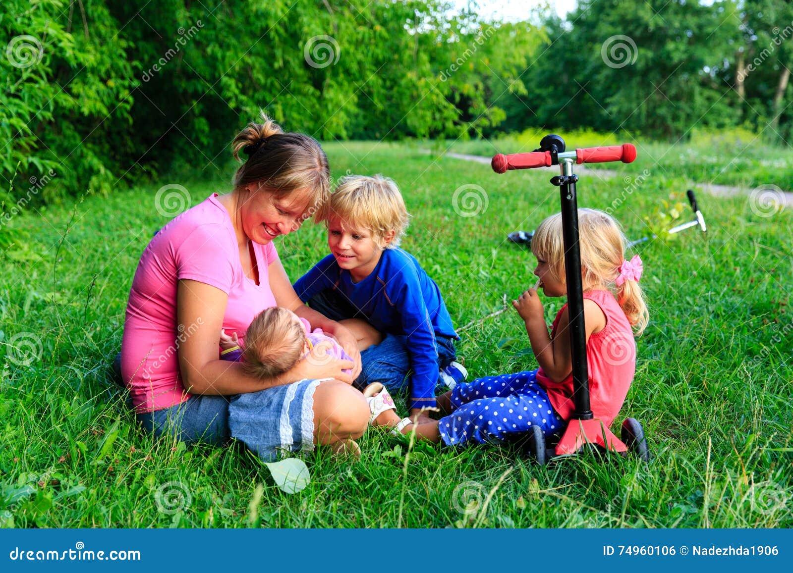 Den lyckliga modern med tre ungar tycker om samvaro i sommar