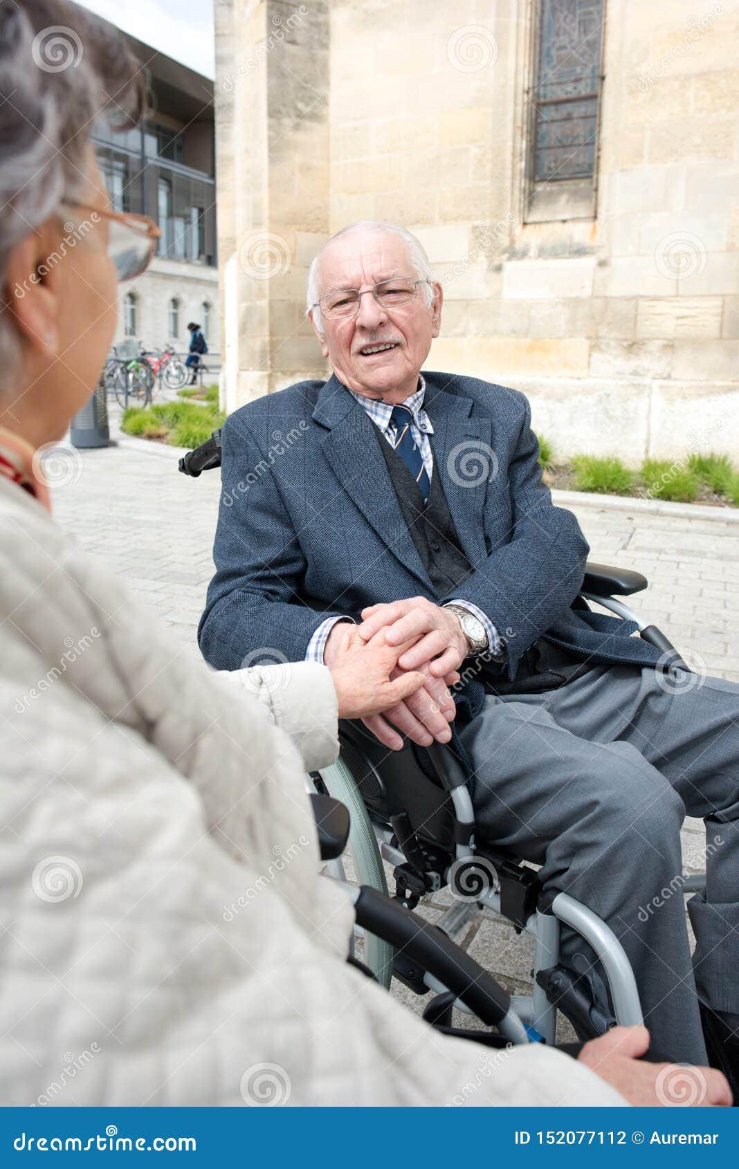Den lyckliga pensionären handikapp par som rymmer händer