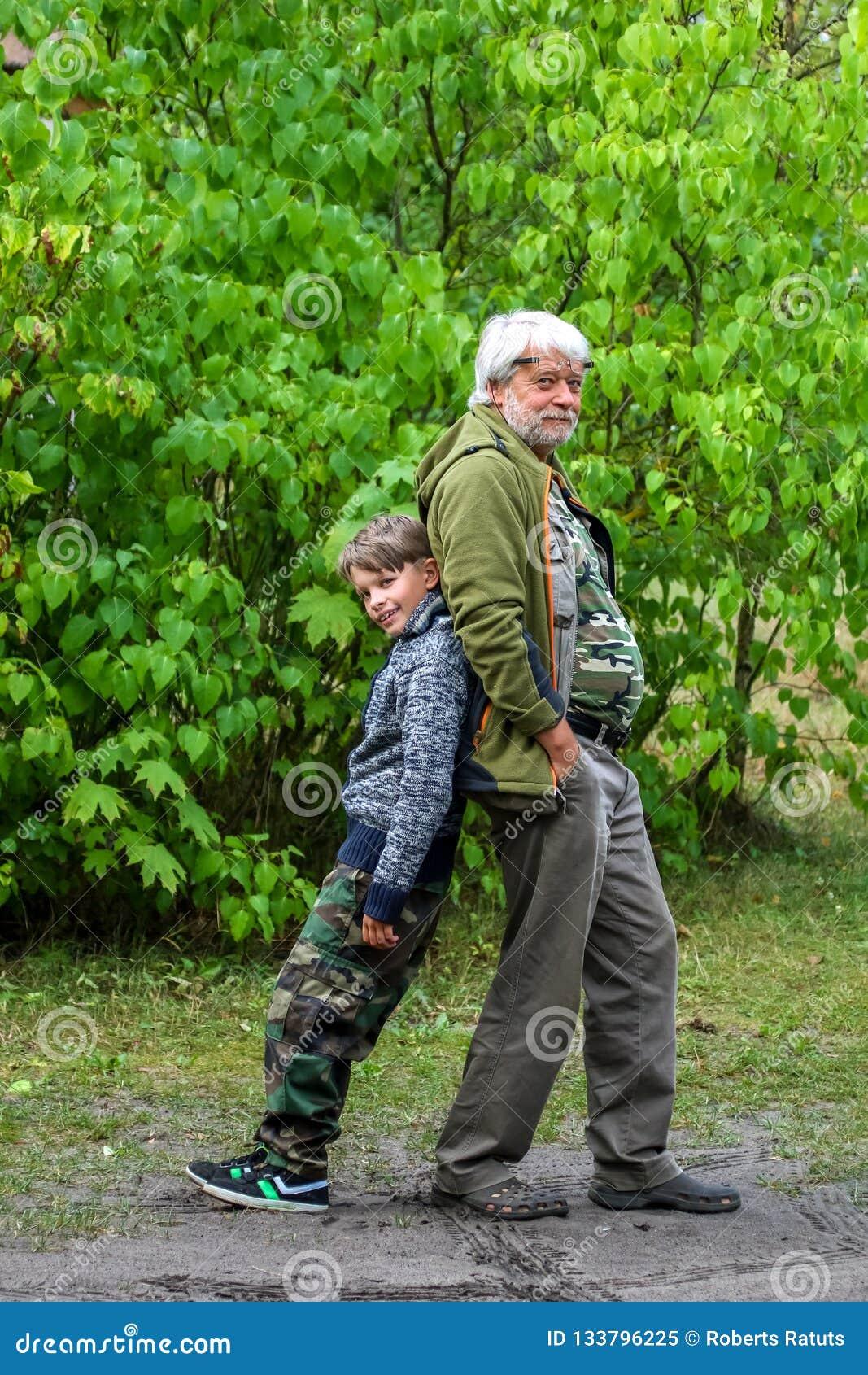Den lyckliga pensionären och pojken i gräsplan parkerar