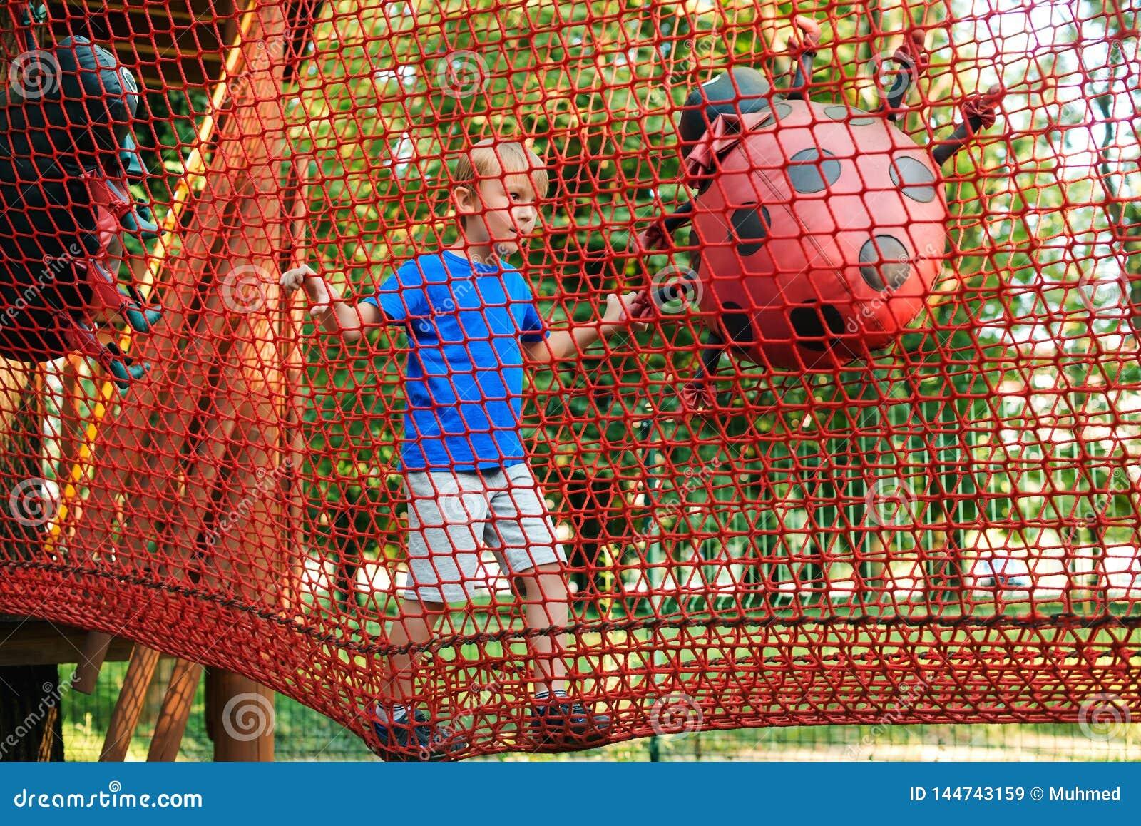 Den lyckliga pojken övervinner hinder i repaffärsföretag parkerar Sommaren semestrar begrepp Den gulliga ungen som spelar på repa