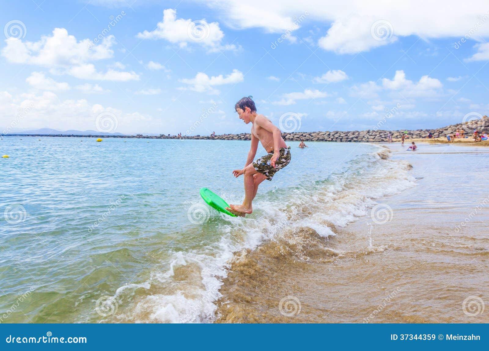 Den lyckliga pojken tycker om att surfa i vågorna