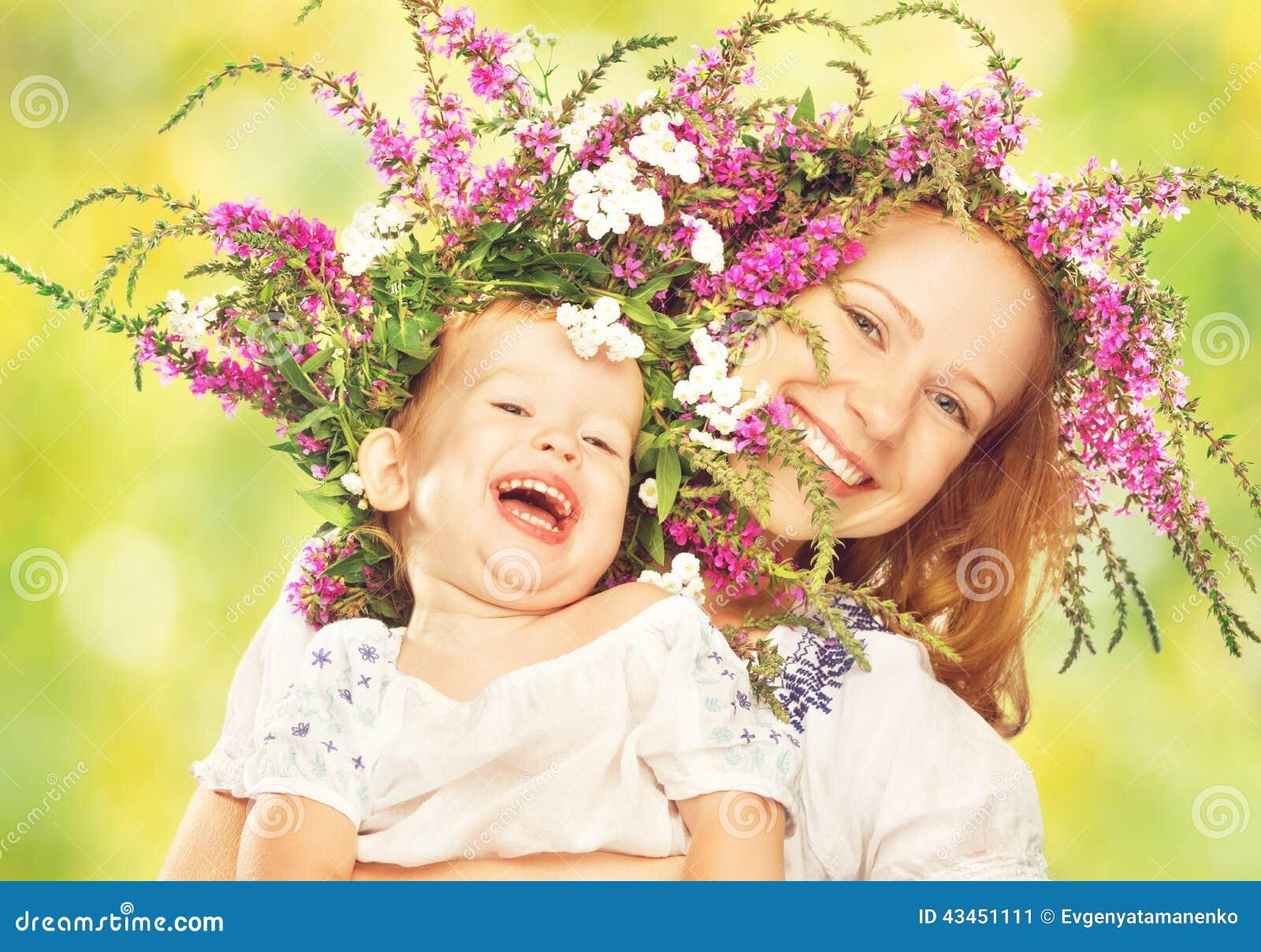 Den lyckliga skratta dottern som kramar modern i kransar av sommar, blommar