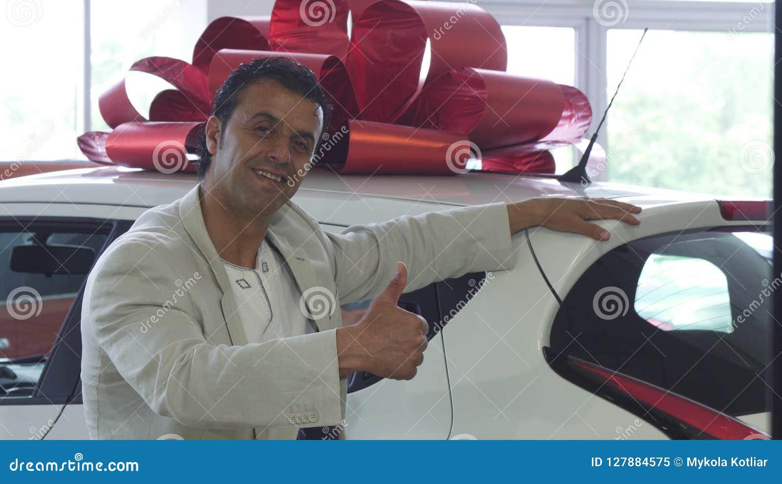 Den lyckliga stiliga mogna manvisningen tummar, upp når den har köpt en bil