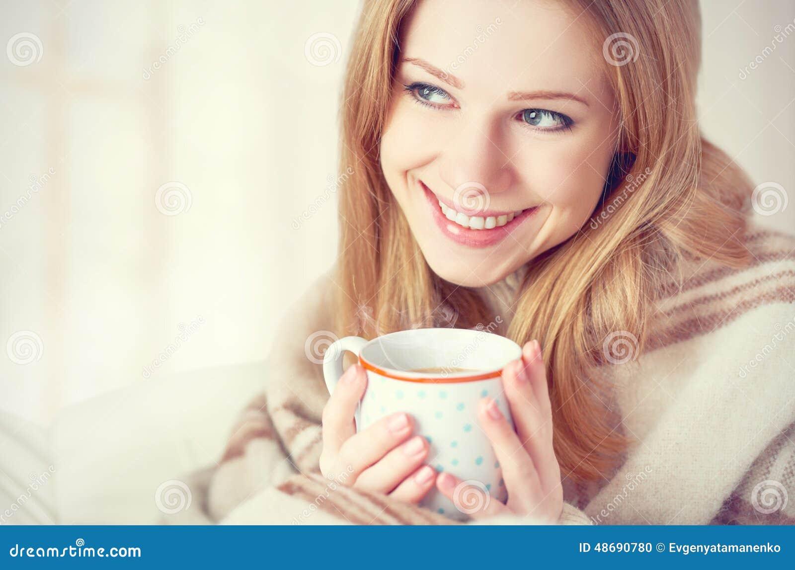 Den lyckliga unga kvinnan är under en filt och en kopp kaffe på vintermorgon hemma
