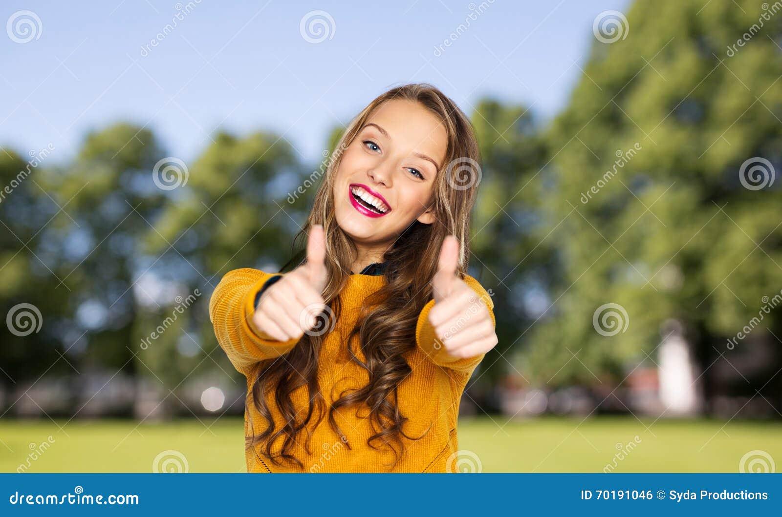 Den lyckliga unga kvinnan eller den tonåriga flickavisningen tummar upp