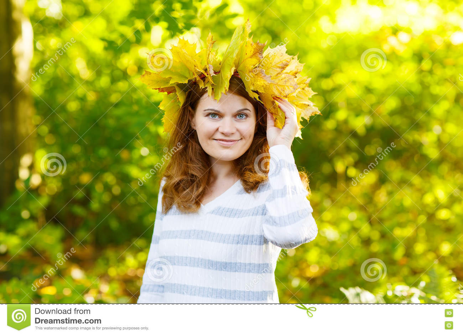 Den lyckliga unga kvinnan med höstlönnlövgirlanden parkerar in