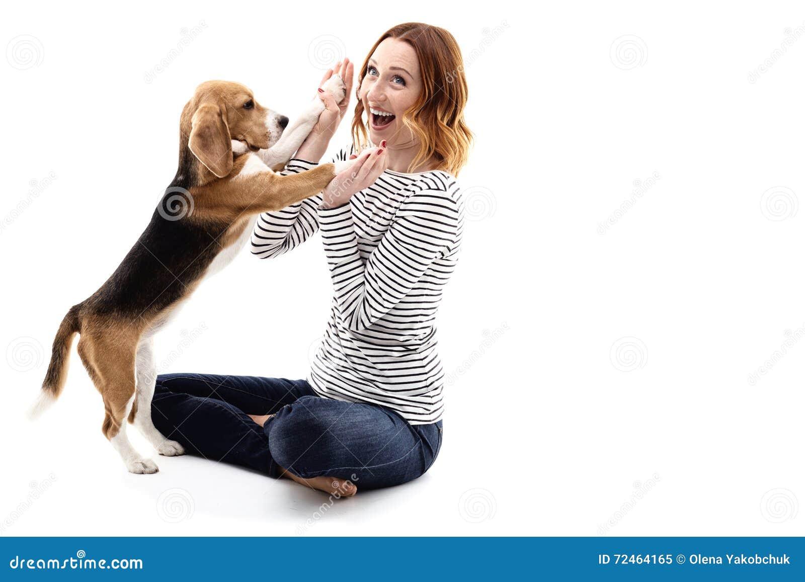 Den lyckliga unga kvinnan spelar med valpen