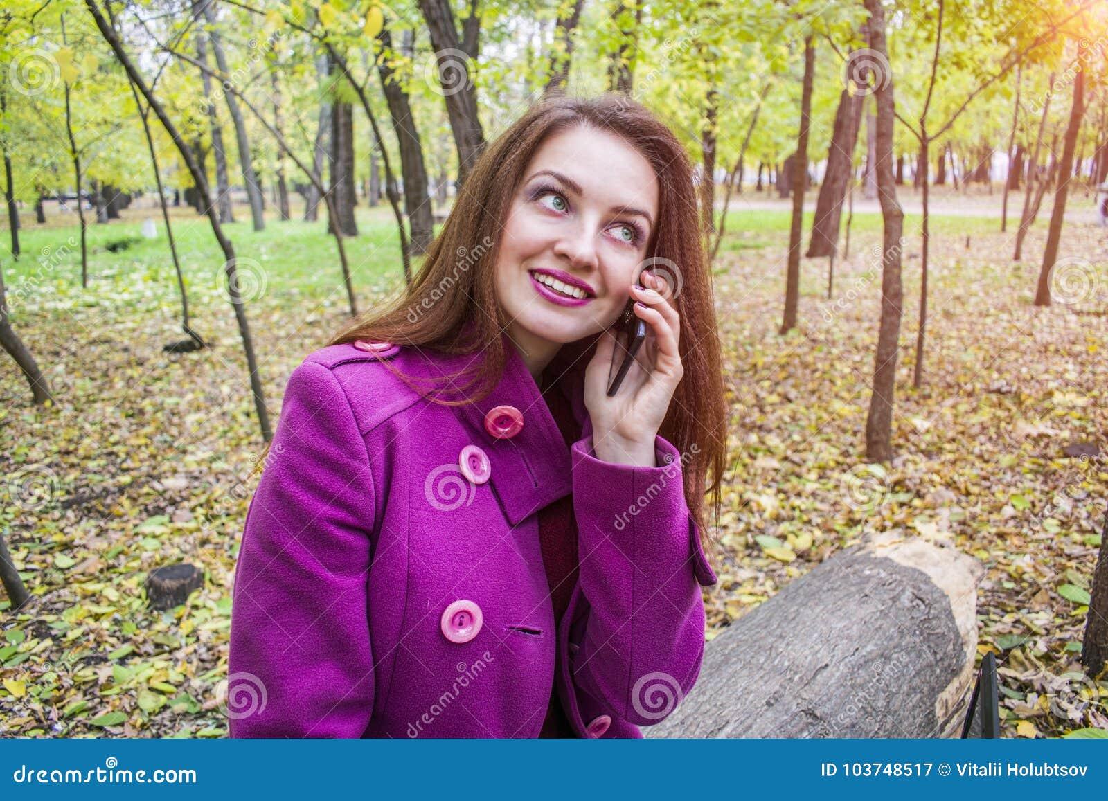 Den lyckliga unga kvinnan talar på en smartphone i hösten parkerar