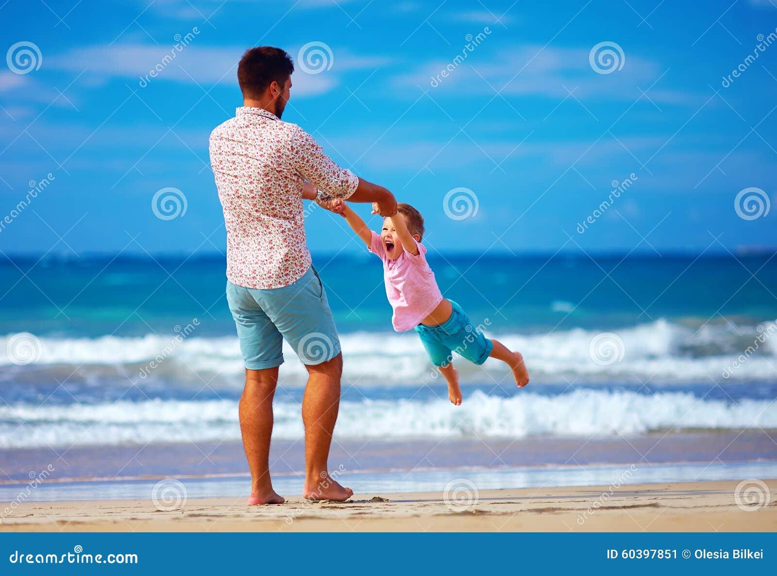 Den lyckliga upphetsade fadern och sonen som spelar på sommar, sätter på land, tycker om liv