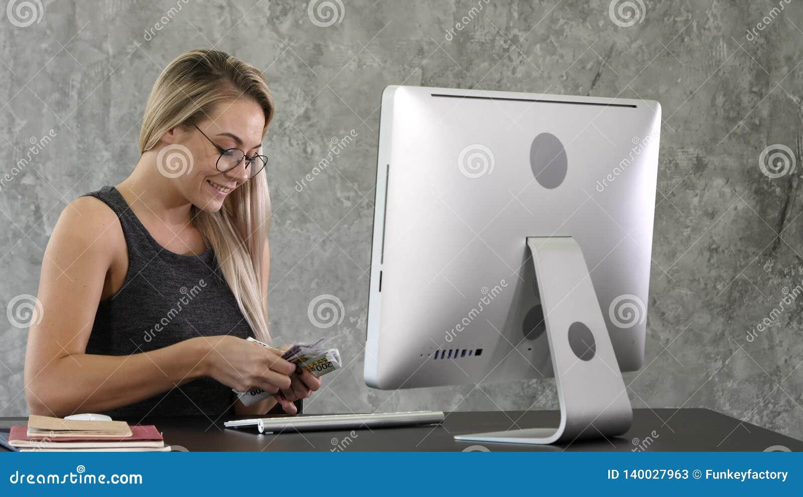 Den lyckliga upphetsade lyckade unga affärskvinnan som rymmer pengardollarräkningar och ser kassa, känner sig förvånad