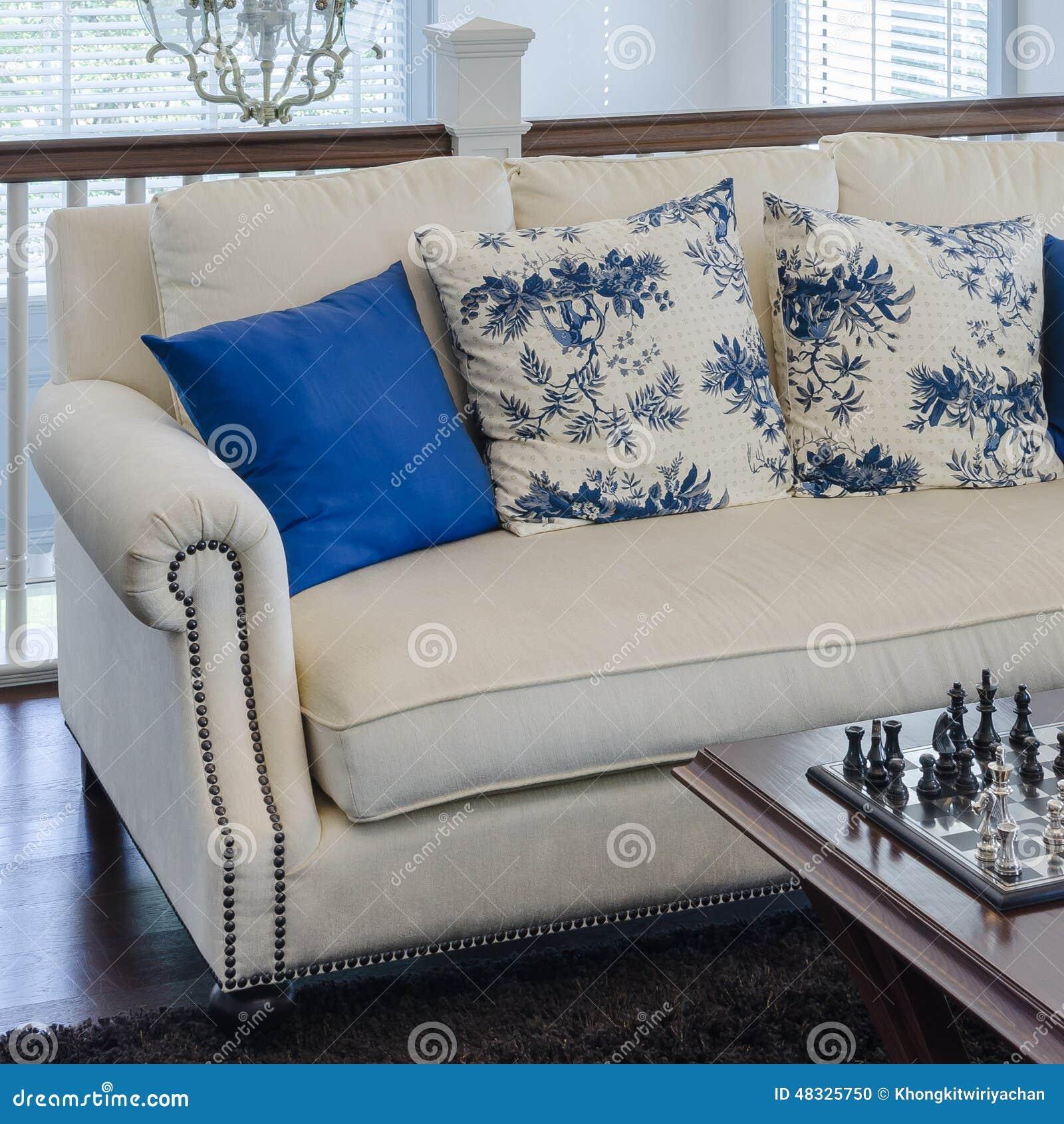 Den lyxiga soffan med blått kudde på brun matta i vardagsrum ...