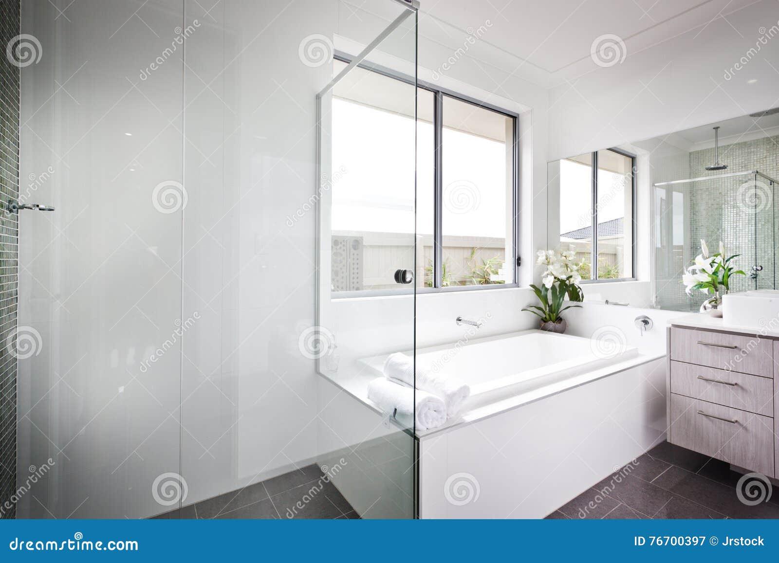 Den lyxiga toaletten med vita väggar och badet badar