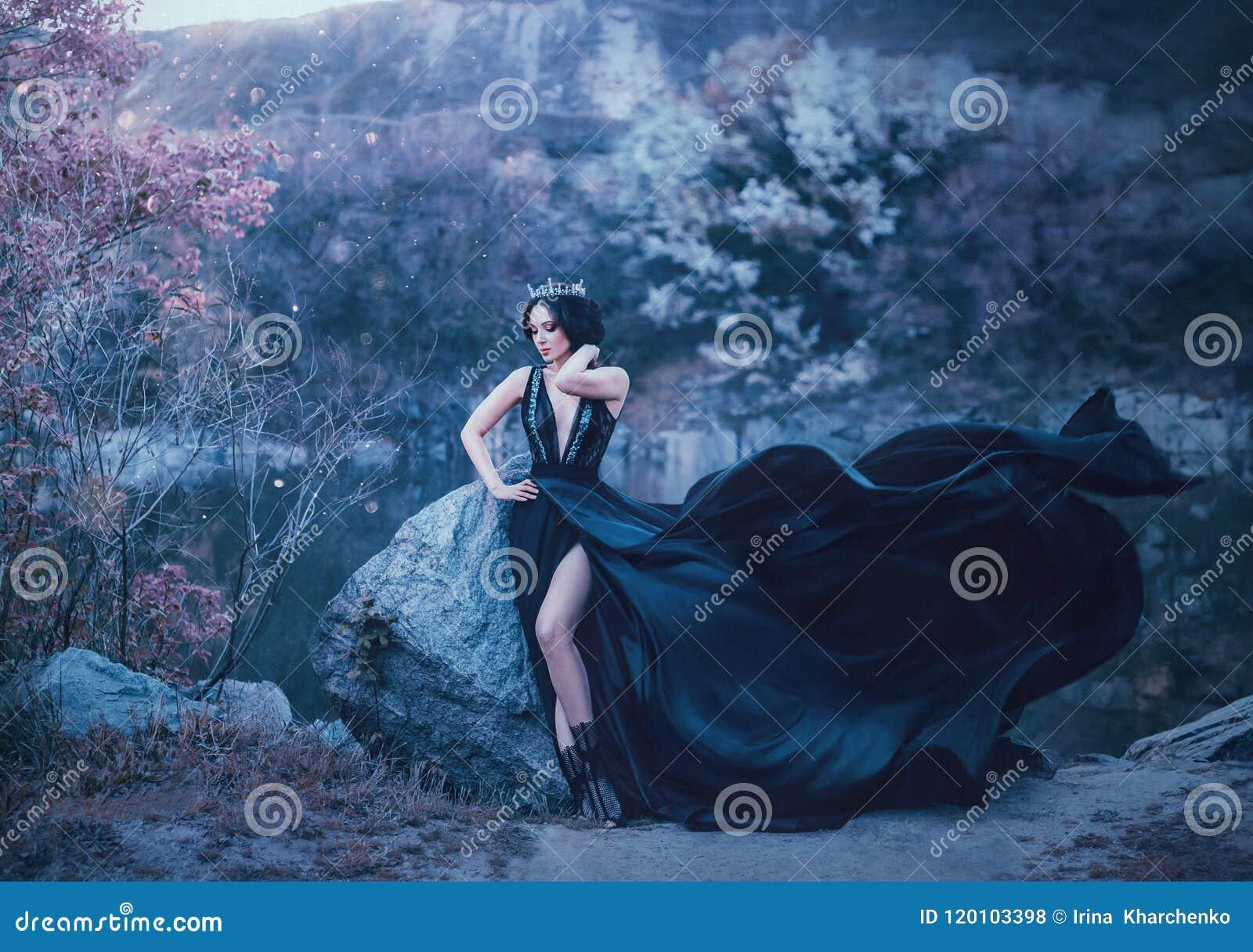 Den mörka drottningen poserar mot bakgrunden av dystert vaggar En lyxig svart klänning med ett långt drev som fladdrar i