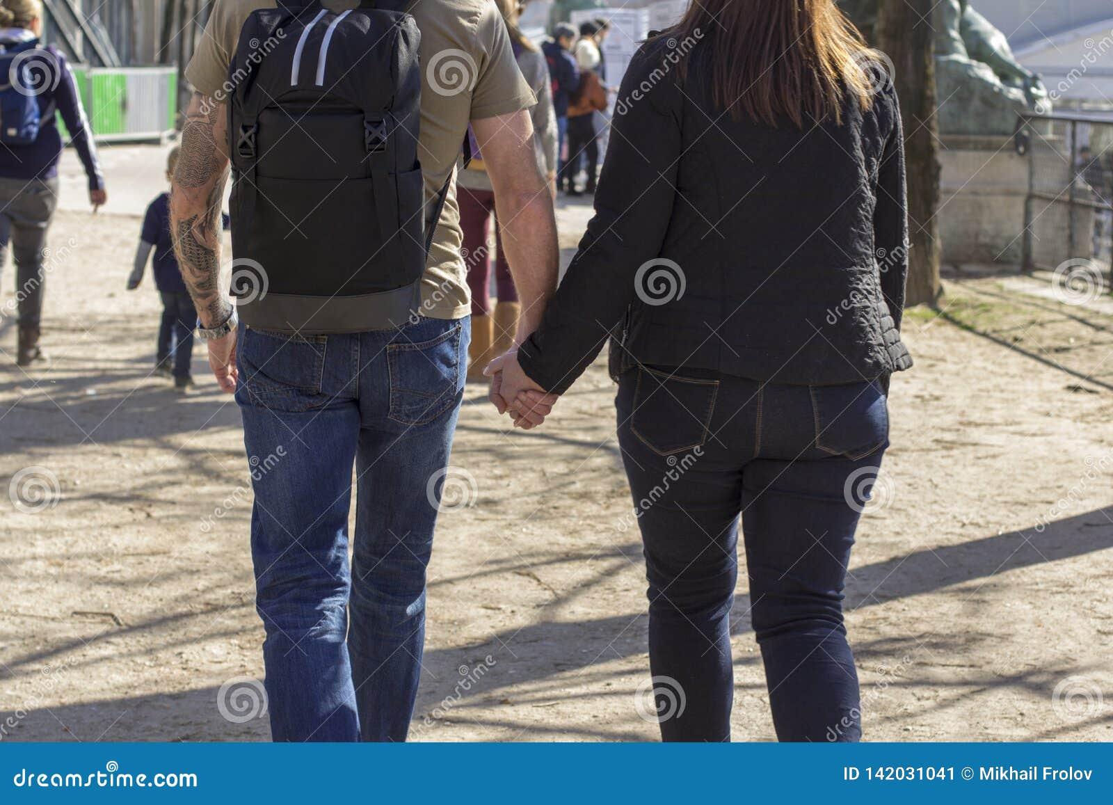 Den magra mannen rymmer handen av en kvinna, medan gå