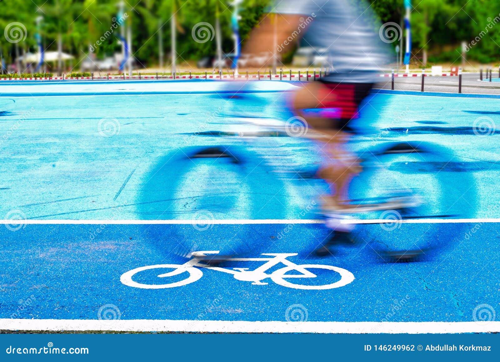 Den manliga cyklisten rider en cykel på gränden av cykeltecknet