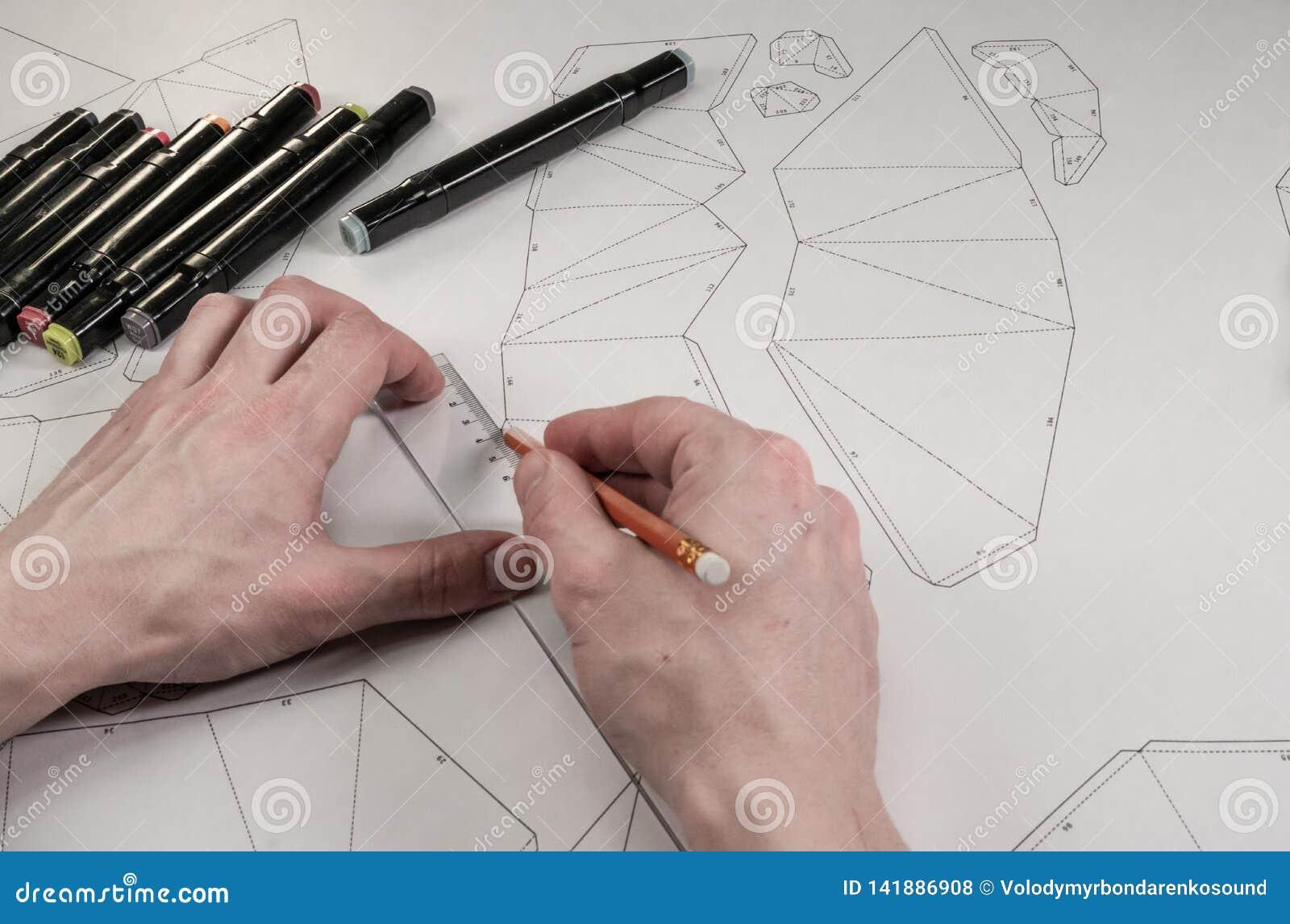 Den manliga formgivaren gör en funktionsduglig teckning Arbetsplats av en leksakformgivare Markörer, linjalen, pennan och blyerts