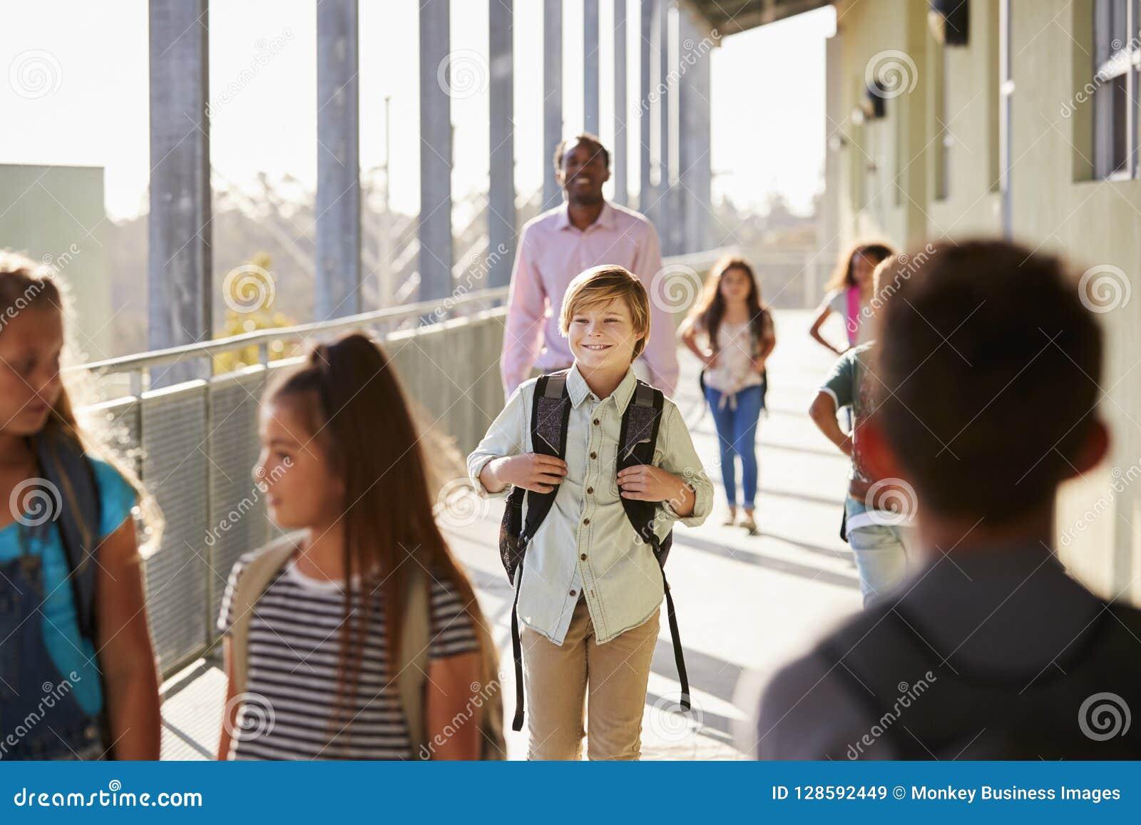 Den manliga läraren och elever går på grundskolauniversitetsområde