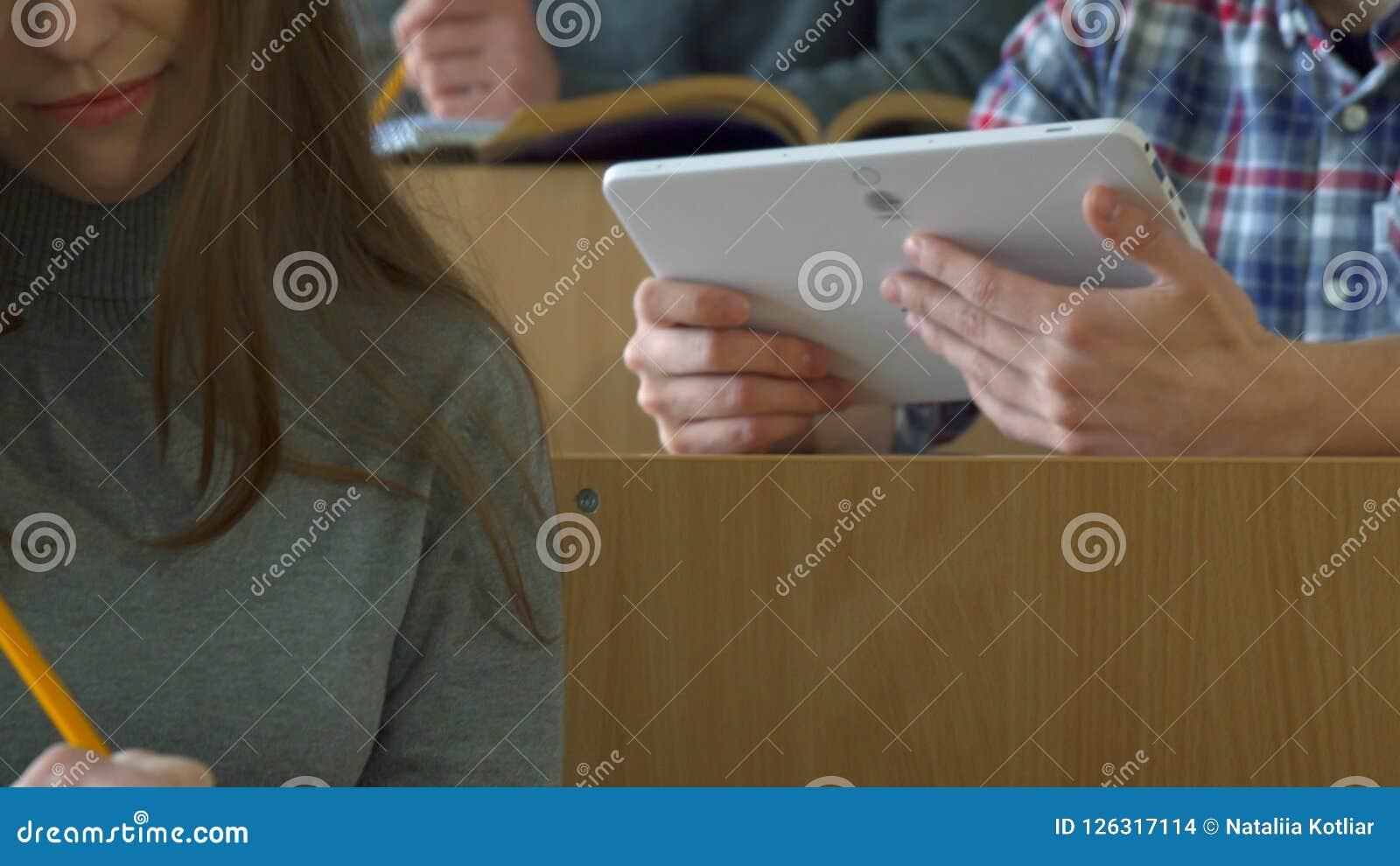 Den manliga studenten visar hans klasskompis något på minnestavlan