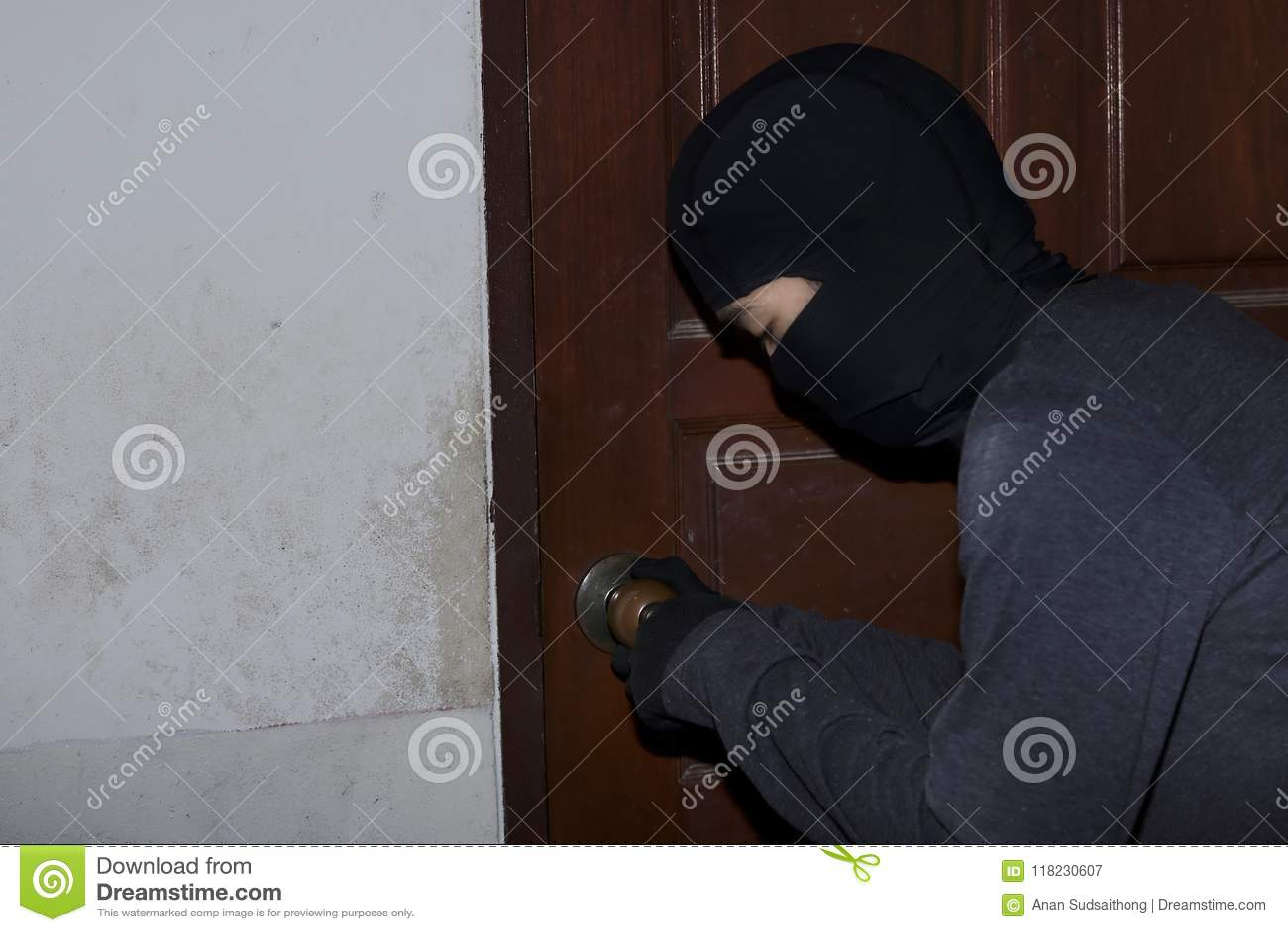 Den maskerade inbrottstjuven med låsplockning bearbetar avbrott och att skriva in in i hus vägg för skugga för pistol för holding