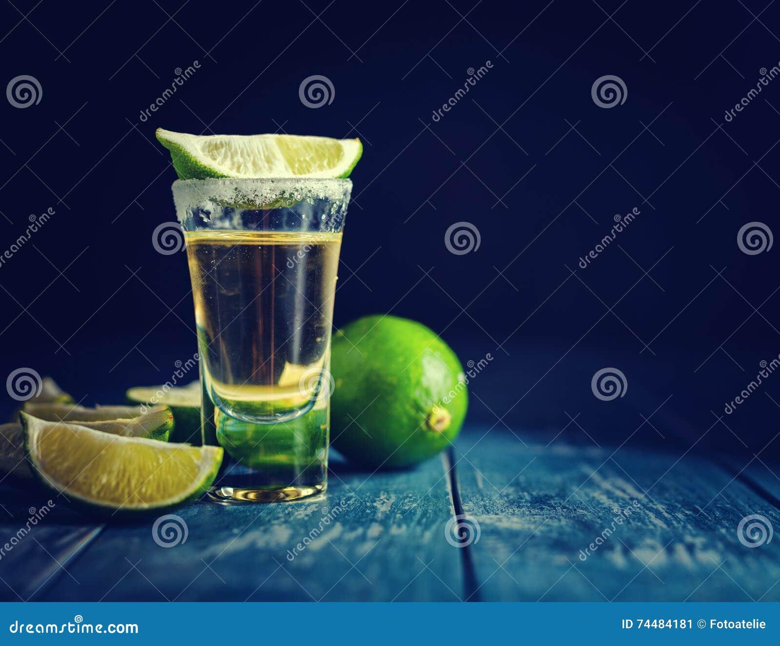 Den mexicanska guld- tequilaen med limefrukt och saltar på trätabellen