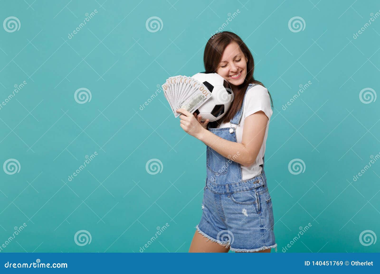 Den mjuka ung flickafotbollsfan med stängda ögon stöttar det favorit- laget med fotbollbollen, fan av pengar i dollarsedlar