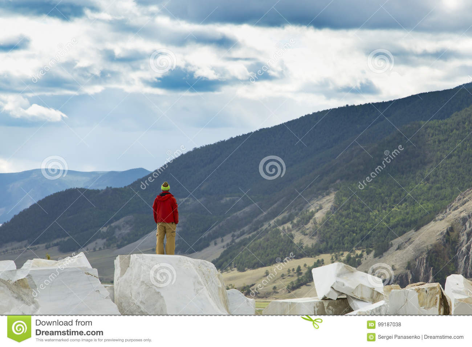 Den moderiktiga grabben i röda ställningar för ett omslag på en marmor vaggar och se in mot sommardalen Sportaffärsföretag- och a