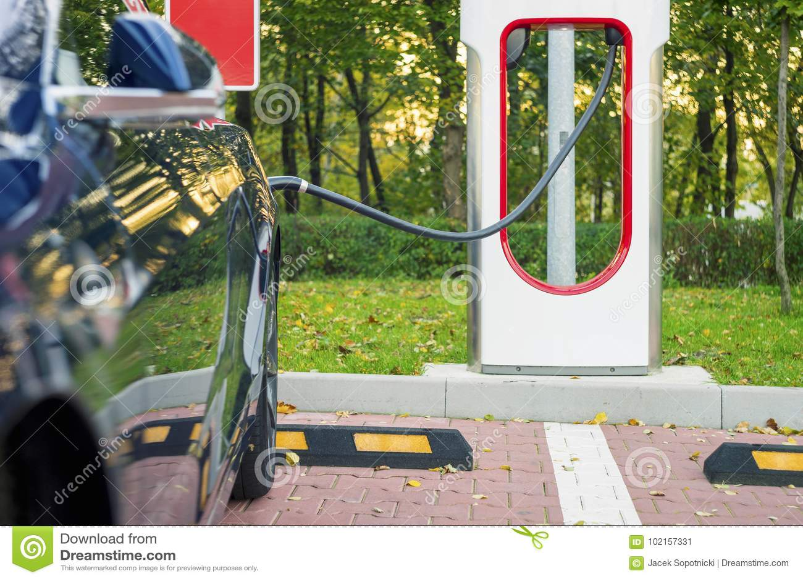 Den moderna elbilen pluggade till uppladdningsstationen i en parkeringsplats