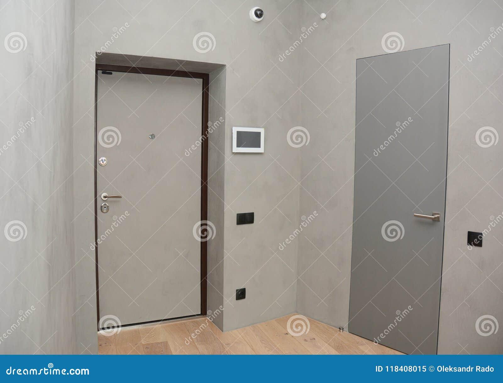 Den moderna inre för dörren för husingångsmetall med säkerhetsCCTV-kameran monteras på rumväggen med brandlarmsystemet