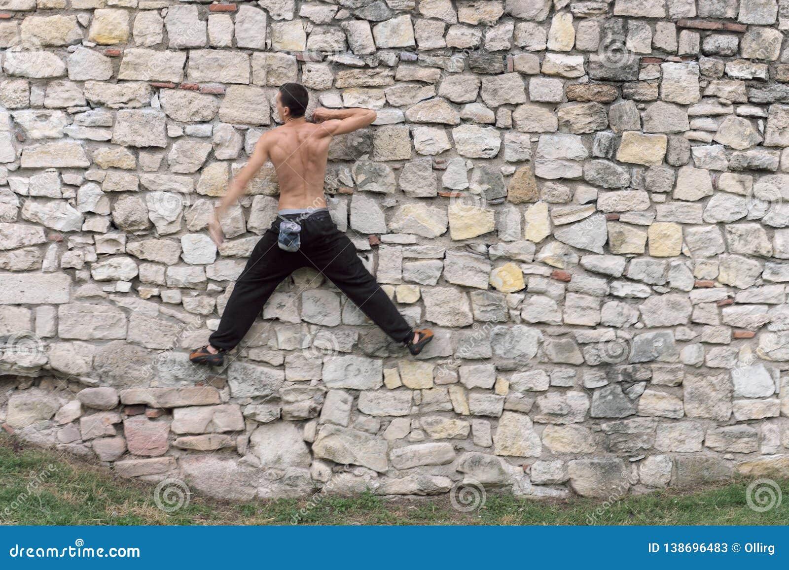 Den muskulösa passformen som är topless av man, utbildar stads- klättring
