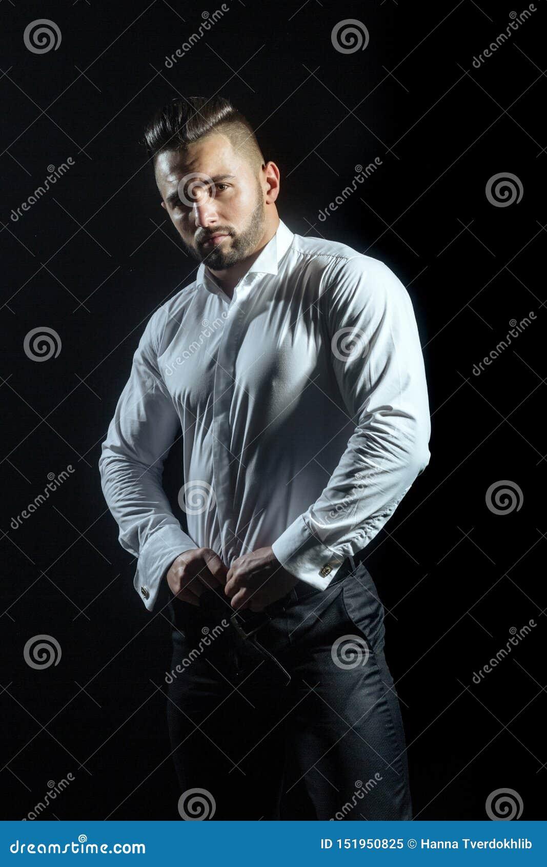 Den muskulösa stiliga grabben på svart bakgrund poserar den bärande eleganta vita skjortan och svart byxa Klänningkod för arbete