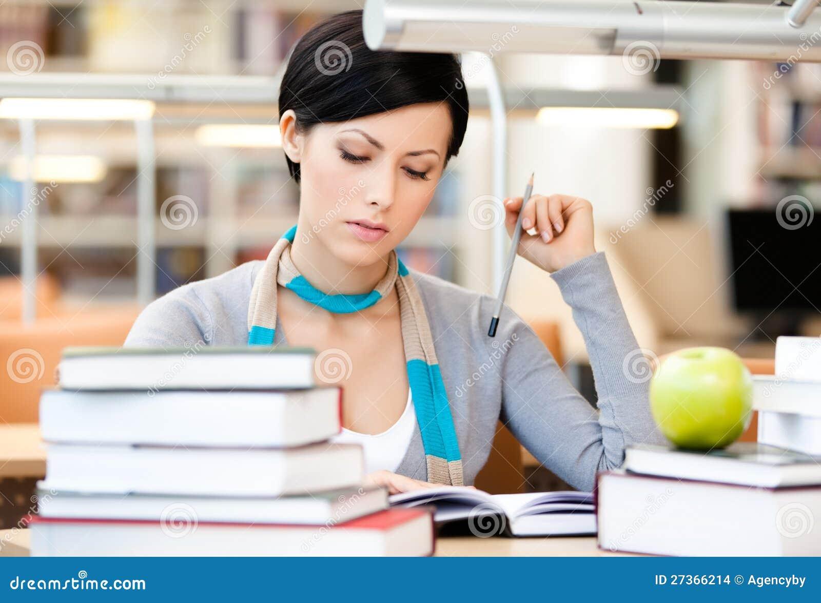Den nätt kvinnan läser att sitta på skrivbordet