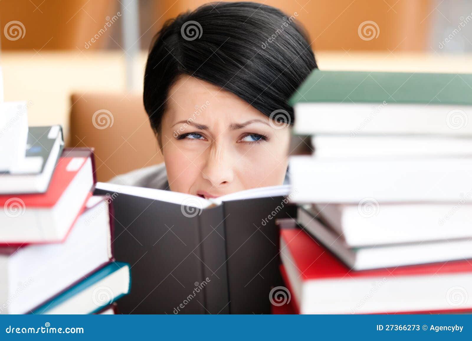 Den nätt kvinnliga deltagaren ser ut över boken