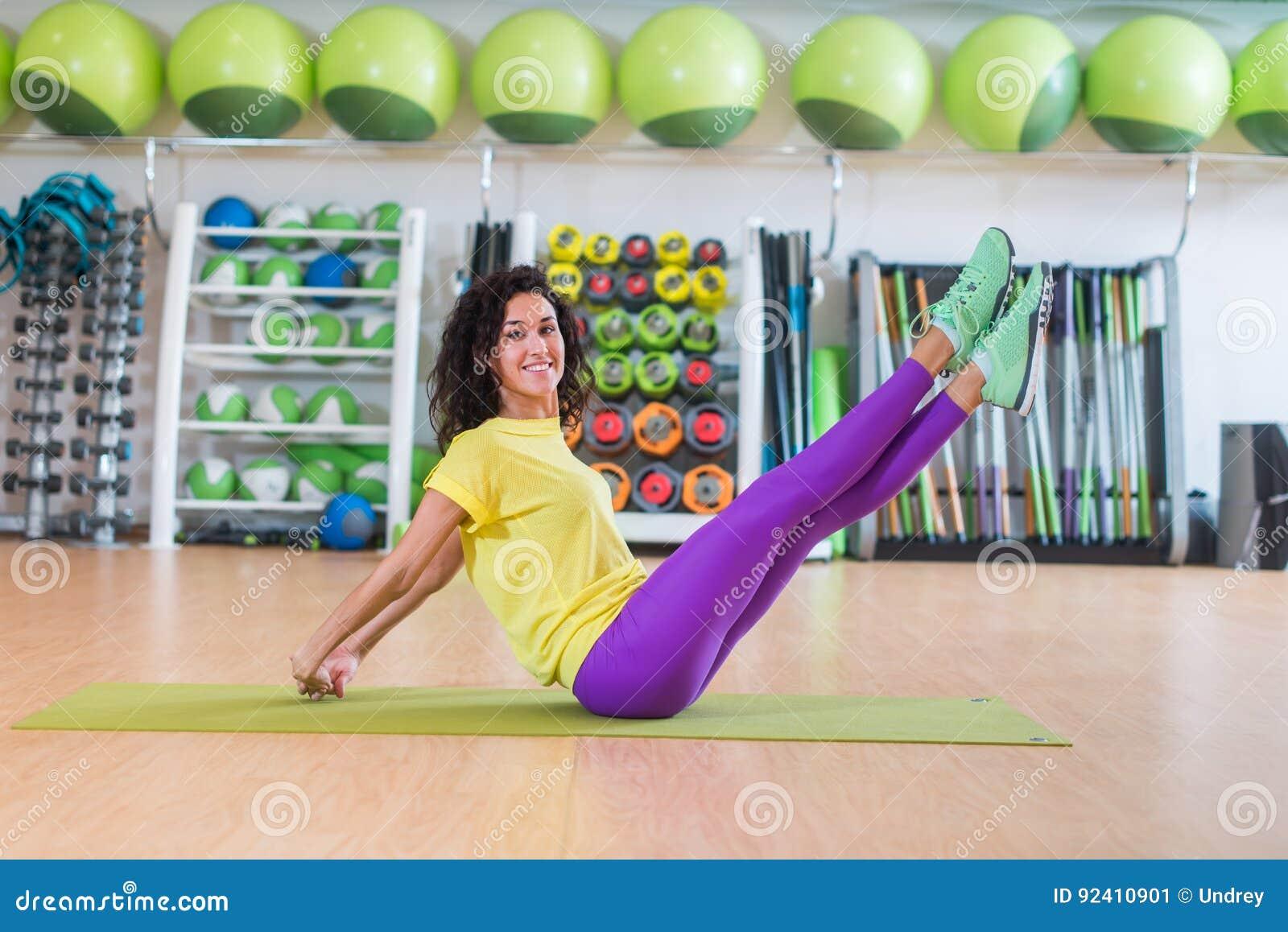 Den nätta konditionmodellen som gör sax, övar sammanträde på golvkorsning, och den uncrossing raksträckan lägger benen på ryggen
