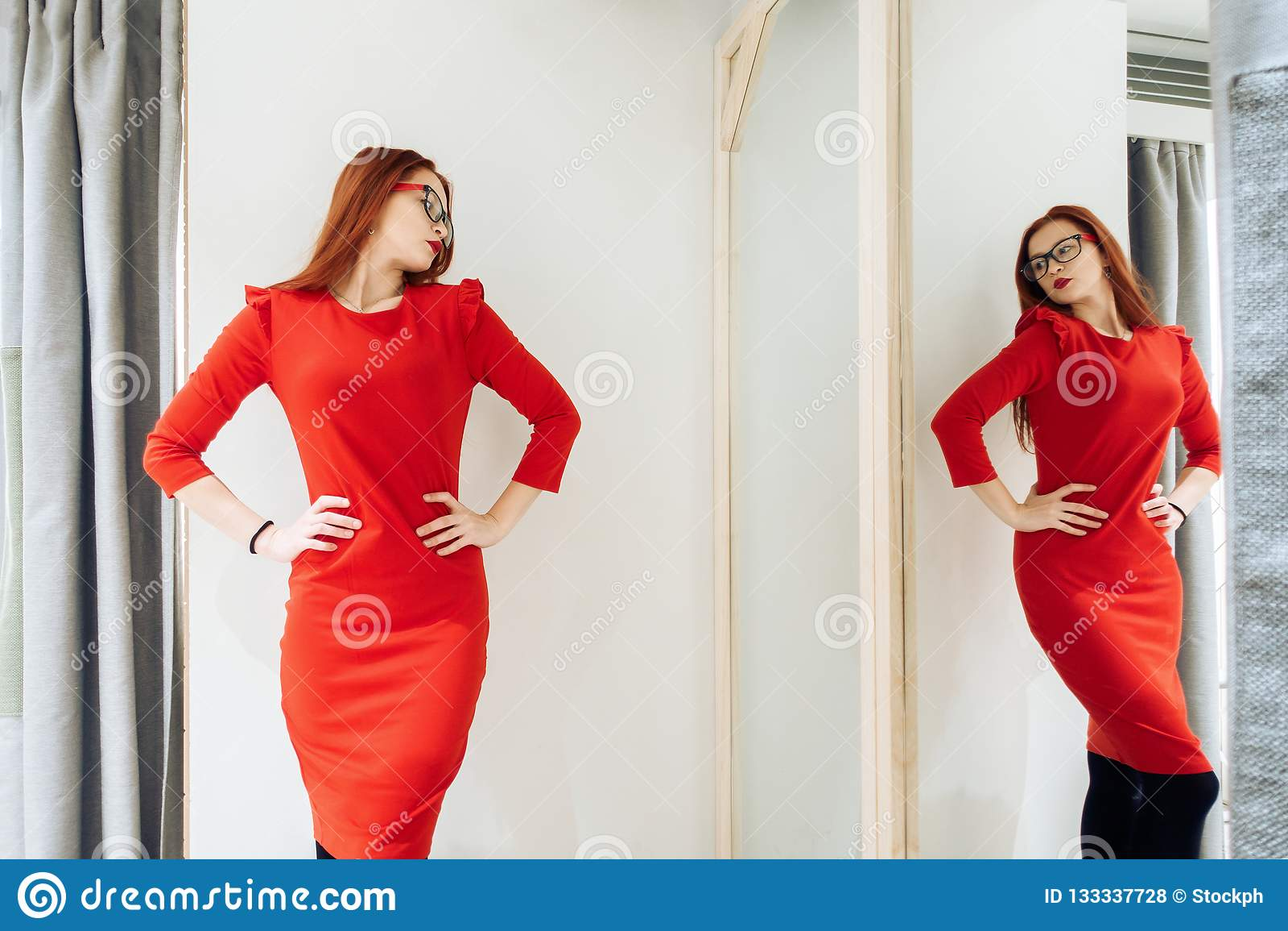 Den nätta kvinnan som försöker på kläder i ett passande, shoppar damen i den röda klänningen reflekteras i spegeln