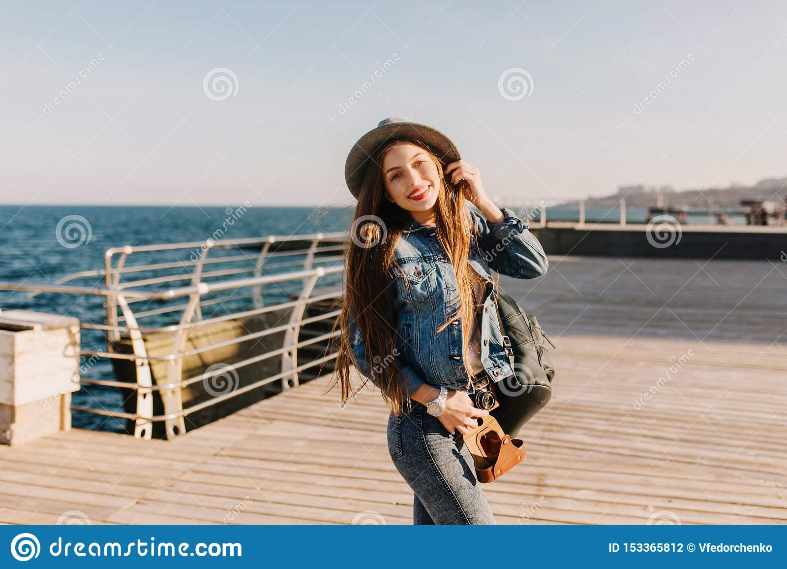 Den nätta le flickan i grov bomullstvilldräkt med brunt hår kom till havet att lyssna till skrik av seagulls Charma brunett länge